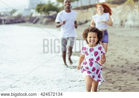 Young Couple And Daughter Running And Enjoying A Beach Day. Summer, Holiday And Family Concept.
