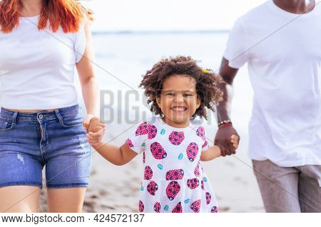 Daughter Walking With Their Parent Along The Beach On Summer Day. Summer, Holiday And Family Concept