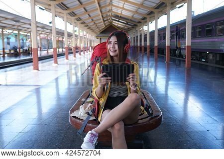 Asian Traveller Play Her Tablet And Listen Music For Wait To Start Journey By Train, Traveling Conce