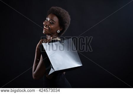 African American Woman Rear View With Afro Hairstyle Holds Black Shopping Bags. Sale And Discounts O