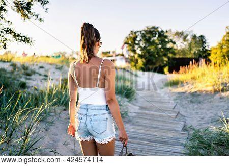 Summer Tan On Skin. Woman Walking On Boardwalk And Leaving The Beach. Stylish Model Wearing Trendy J