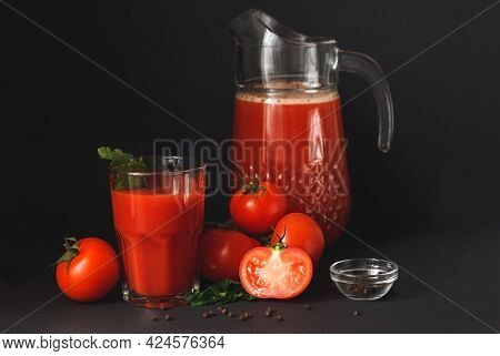 Fresh Tomato Juice In A Glass With Tomatoes On A Dark Background. Vegetable Tomato Drink For A Healt