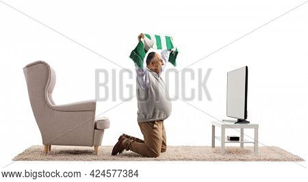 Mature man kneeling in front of a tv and cheering with a scarf isolated on white background