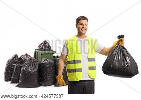 Waste collector holding a plastic bag in front of a bin and a pile of bags and smiling at camera isolated on white background