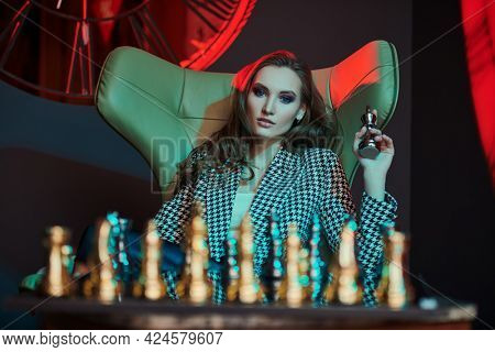 Elegant business lady in stylish suit plays chess in a modern luxury interior. Fashion shot. Business style.