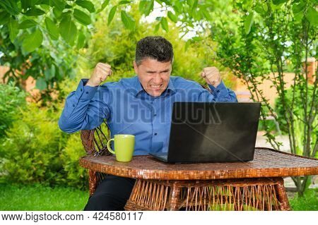 Middle-aged Angry Businessman Clenches His Fists And Grits His Teeth In Anger While Sitting Near Lap