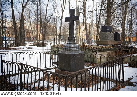 Grave With Black Cross In Snowy Cemetery With Leafless Trees, Residential Buildings In The Distance