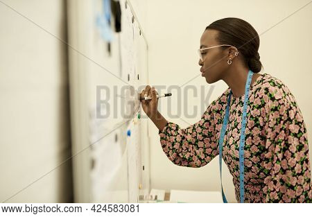 Young African Female Fashion Designer Writing Notes On A Whiteboard