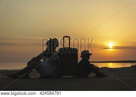 Mother And Young Son With A Suitcase On The Background Of The Sunset Waiting .a Trip To The Sea, A V