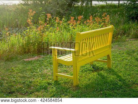The Sun Shining Down On A Yellow Garden Bench.