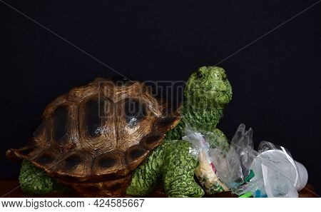 Figurine Of A Decorative Turtle And Plastic Trash On A Black Background