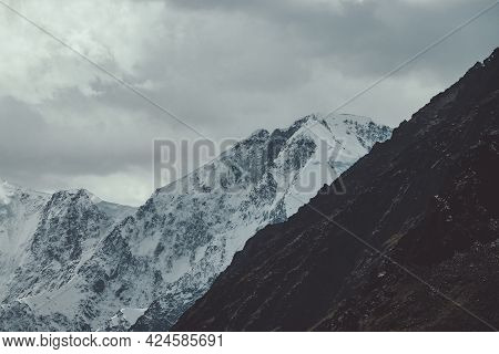 Atmospheric Landscape With Great Snowy Mountain Wall In Clouds. Gloomy Mountain Scenery With High Sn