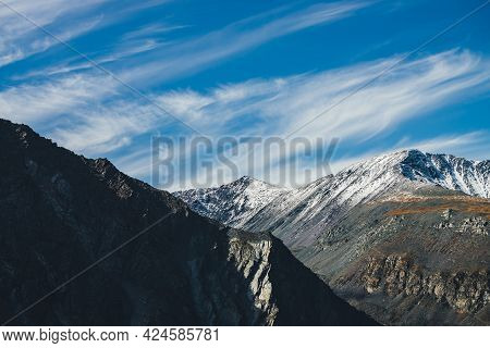 Scenic Mountain Landscape With Snowy Pointy Top In Autumn Colors In Sunshine Under Cirrus Clouds In