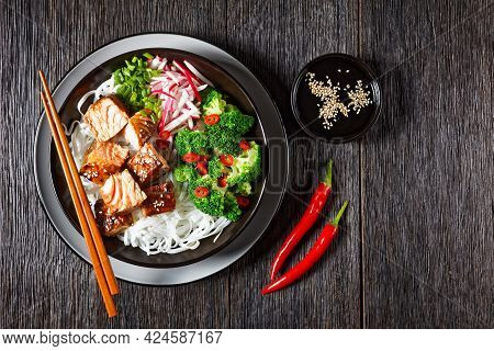 Salmon Teriyaki With Rice Noodle, Broccoli, Radish And Green Onion In A Bowl With Chopsticks On A Da
