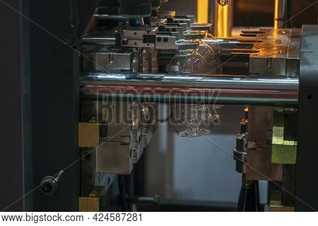 The Plastic Drinking Bottles In The  Blowing Mold Machine. The Operation Of Pet Bottle Processing By