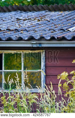 Vintage Gray Roof, Broken Window And Red Wooden Wall