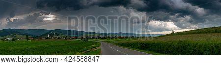 Panoramic Image, Asphalt Road Leading To A Small Hungarian Village In Transylvania, Romania, Dramati