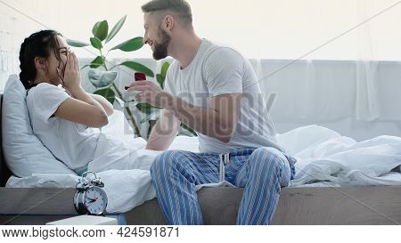 Happy Bearded Man Holding Red Box With Wedding Ring While Doing Proposal To Girlfriend In Bedroom.