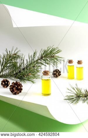 Essential Pine Oil In Small Glass Bottles With Branches And Cones On Curved Sheet Of White Paper On