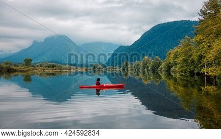 Adventure Caucasian Adult Woman Kayaking In Red Kayak Surrounded By Canadian Mountain Landscape. Art