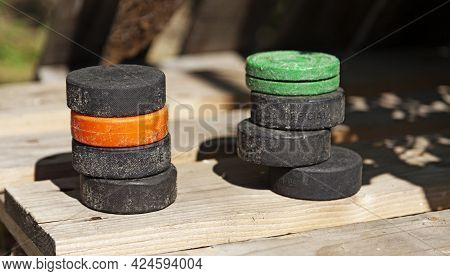 Two Piles Of Well-used Hockey Pucks At My Home