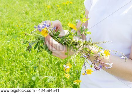 The Girl Weaves A Wreath With Wildflowers And Meadow Grasses. Decoration For The Traditional Slavic