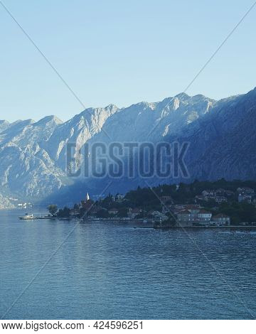 A View Of Montenegro From The Waters Of The Adriatic Sea. Sunlight Streaks Across The Mountainous Cl
