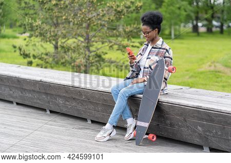 Happy Mixed Race Woman Skateboarder Read Chat Messages In Smartphone Relaxed After Skateboarding Tra