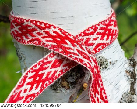 Red And White Ribbon With Ornament Of Traditional Slavic Signs Tied On A Birch. Celebrating Summer S