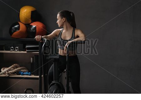 Portrait Of Female Athlete On Air Bike At Fitness Gym. Sporty Fit Woman Resting While Doing Cardio E