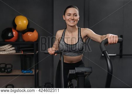 Portrait Of Smiling Fitness Woman Using Air Bike For Cardio Workout And Exercising Her Legs At Gym.