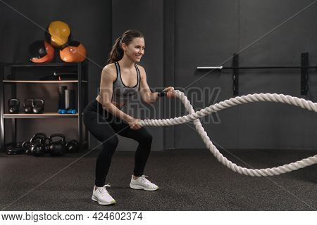 Muscular Young Smiling Woman Working Out With Battle Ropes At Dark Gym, Intense Functional Circuit T