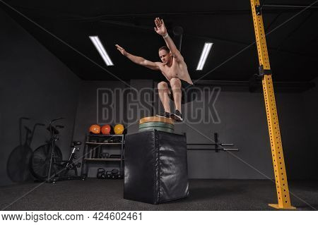 Professional Athlete Doing Box Jump Exercise As Part Of Functional Circuit Training At Dark Gym. Str