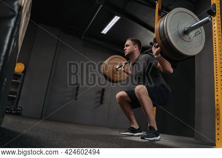 Muscular Caucasian Man Lifting Weights And Doing Back Squat In Gym. Attractive Athlete Is Holding A