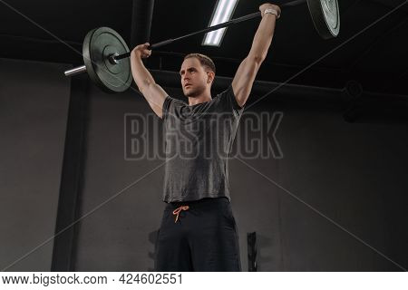 Strong Muscular Man Holding Heavy Barbell Overhead At Dark Gym, Doing Military Press Exercises As A