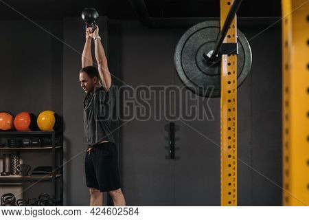 Muscular Weightlifter Doing An Exercise With Kettlebell At Dark Gym With Professional Sport Equipmen