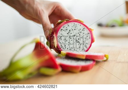 Female Hands Is Cutting A Dragon Fruit Or Pitaya With Pink Skin And White Pulp With Black Seeds On W