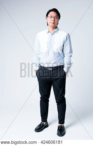 Handsome Young Asian Businessman In Shirt And Trousers Stands With Hands In Pockets