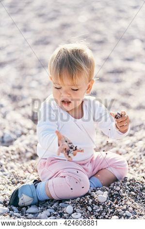 Cute Baby Sitting On A Pebble Beach And Holding Small Pebbles In His Hands
