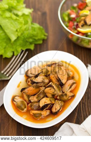 Mussels In Sauce On White Dish On Wooden Background