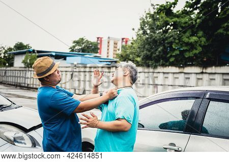 Two Asian Middle-aged Fat Man Are Arguing, Due To A Accident Car Crash, While It Was Raining, To Peo