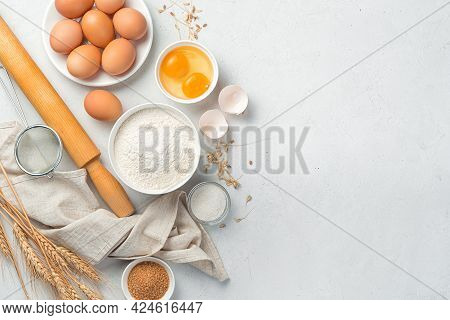 Flour, Eggs, Sugar, Rolling Pin On A Gray Background. Ingredients For Baking. Top View, Copy Space.