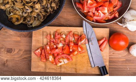 Cooking A Vegetarian Dish Of Mushroom And Tomato Stew - Sliced Champignons In A Pan, Sliced Tomatoes