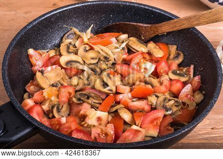 Cooking A Vegetarian Dish Of Mushroom And Tomato Stew - Sliced Fried Mushrooms And Tomatoes In A Pan
