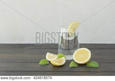 Clear Water In Transparent Glass With Slice Of Lemon, Cutted Lemons And Mint Leaves On Dark Wooden B