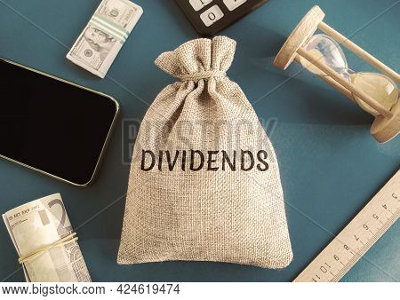 Money Bag With The Word Dividends. Payment Made By A Corporation To Its Shareholders As A Distributi