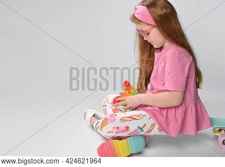 Happy Little Red-haired Girl, Rejoice, Shot Into The Studio Of A Toy Butterfly. Baby Sitting On A Sk