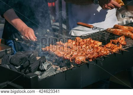 Hands Cook With Skewers Of Kebabs, Meat, Bbq Cooking, Grill, Smoke Close-up Outdoors. Backyard Barbe