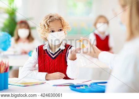 Kids In Face Mask In School Class. Teacher With Hand Sanitizer. Sanitizing In School. Student Child