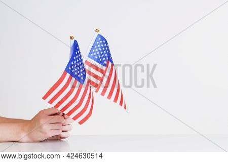 American Flags In Hands On A Light Background Over The Table.stars And Stripes Flag Setting.presiden